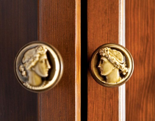 The author raided his collection of vintage hardware for knobs to adorn the new linen press, including these cameos from Low Art Tile.