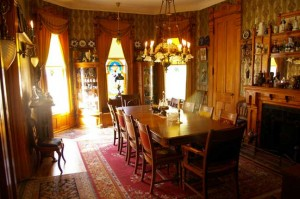 At the Babcock House in Manistee, Michigan, the dining room's period decor takes its cue from the windows, with multiple, identical curtain treatments and mirror-image china cabinets.