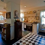 The kitchen occupies space carved out for it in the 1870s, when a cookstove stood at the central chimney (now boxed in). A painted floor and checkerboard floorcloth underlie classical details and modern function.