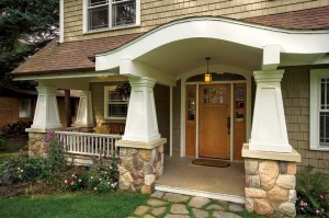 An open porch, square tapered columns, and a stone foundation create a historical Craftsman feel for this new home in Michigan.