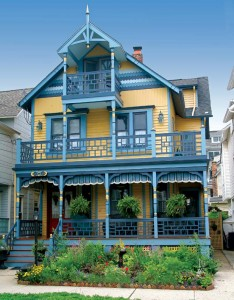 A third-story balcony perches above the main porch on a classic Stick Style house.