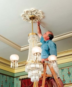 Steve Jordan touches up a medallion in the double parlors of the Landmark Society of Western New York.