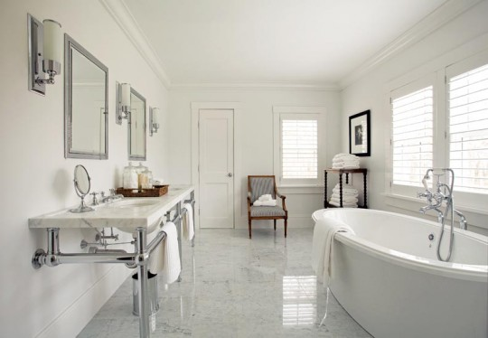 Marble flooring, a soaking tub, and a five-legged marble washstand offer simplicity and authenticity to this new old bathroom.