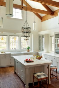 Wood flooring, exposed beams, and vintage-inspired drawer pulls offer an old-time feel in this Hutker Architects kitchen.