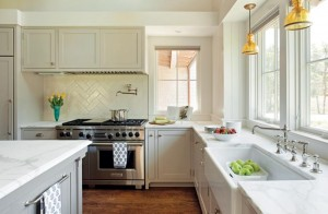 Shaker-style cabinetry and marble countertops offer a traditional feel in this new farmhouse on Martha's Vineyard designed by Hutker Architects.