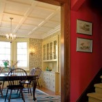 The dining room's coffered ceiling with dentil molding is on view from the front hall.