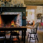 A farmhouse table is set in front of the fireplace, designed to resemble a pioneer cooking hearth.