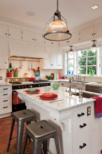 In this 1904 kitchen, the white cabinets, subway tile, and Carrara marble countertops are punctuated by black glass hardware and colorful accessories.
