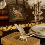 An antique Asian ivory dragonfly perches amidst decorative objects on the dining table.