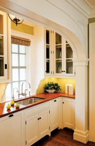 Crown Point Cabinetry set this pantry in an alcove and used historically inspired glass doors and  beadboard to give the space a traditional look.
