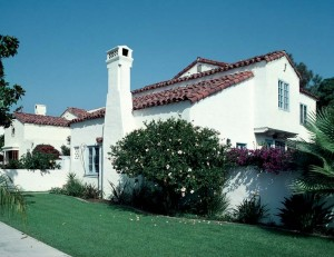 Part of a group of picturesque Spanish Colonial Revival houses of the 1920s in Coronado, California, this house displays the rambling, asymmetrical massing and prominent chimneys of its style, all unified by white stucco walls and a red barrel-tiled roof.