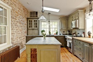 A mix of natural materials (such as wood and stone) and two-tone cabinets creates a handsome new old house kitchen.