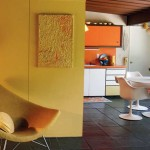 Walls in high-style mid-century homes often were treated to greens that tended toward acid, or tangerine with a pinkish cast. Both pop against whites and the dark stone floors.