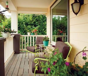 Cased beams and simple railings help to frame a front porch sitting area, while an oversized picture window invites the outside in.