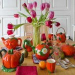 On the kitchen table, tulips from the garden add even more color. Andrea Brock collects teapots; this is part of her whimsical collection.