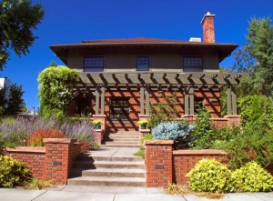 The upper story and pergola of this Foursquare take cues from the mossy green of the variegated brickwork.