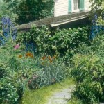 The archival photo shows a lushly planted cottage garden in front of Convery Farmhouse.