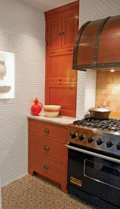 Next to the stove, birch cabinets have the look of built-ins; the porcelain mystery object now commands a place of honor (at left) in the cooking area.