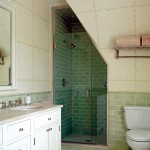 The bathroom has traditional green subway tiles in the shower stall.