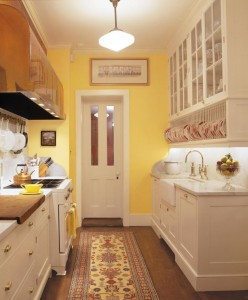 A vintage-looking stove, copper hood, and marble countertops contribute to the 1920s feel of the small galley kitchen.