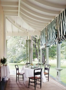 Striped shades on the back porch continue the theme of the metal roof overhead.