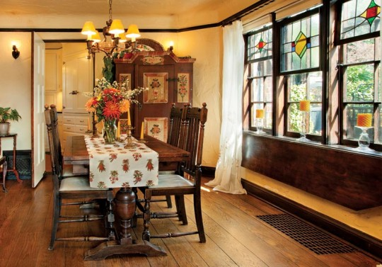 Original stained glass windows light the dining room, which features another built-in drop-leaf table below the windows.