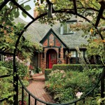 A veritable garden of Eden surrounds the house, seen here through the iron fence and arbor installed by a previous owner.