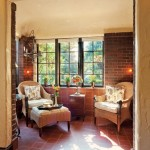 The conservatory welcomes sunlight through its paned windows into the cozy brick-lined room.