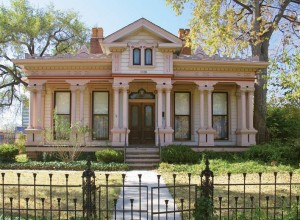 The richly ornamented 1873 Kemper House displays a notable High Victorian front porch with paired columns and fancy gingerbread.