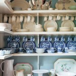 China and cookware are beautifully displayed in a new pantry that looks original.