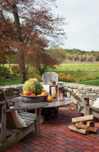 A traditional New England dry-laid stone wall rings a patio that has a view of the painterly surroundings.
