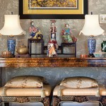 The tortoiseshell console table probably dates to the 1920s; tucked under is a pair of chinoiserie stools.