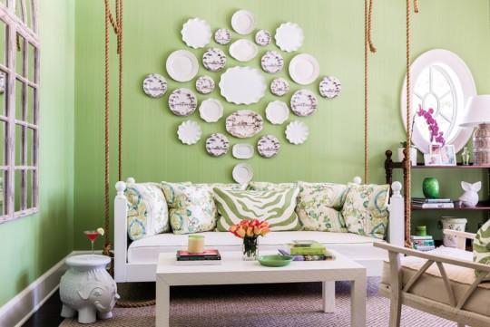 Instead of a picture, a swinging sofa is crowned with ceramics.
